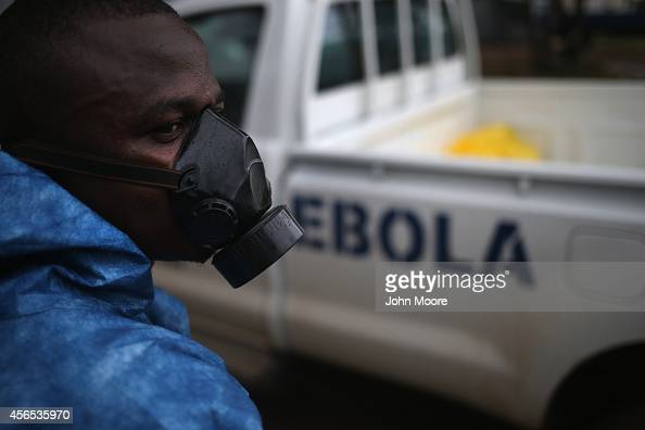 A health worker watches as a burial team collects Ebola victims from a Ministry of Health treatment center for cremation on October 2 2014 in...