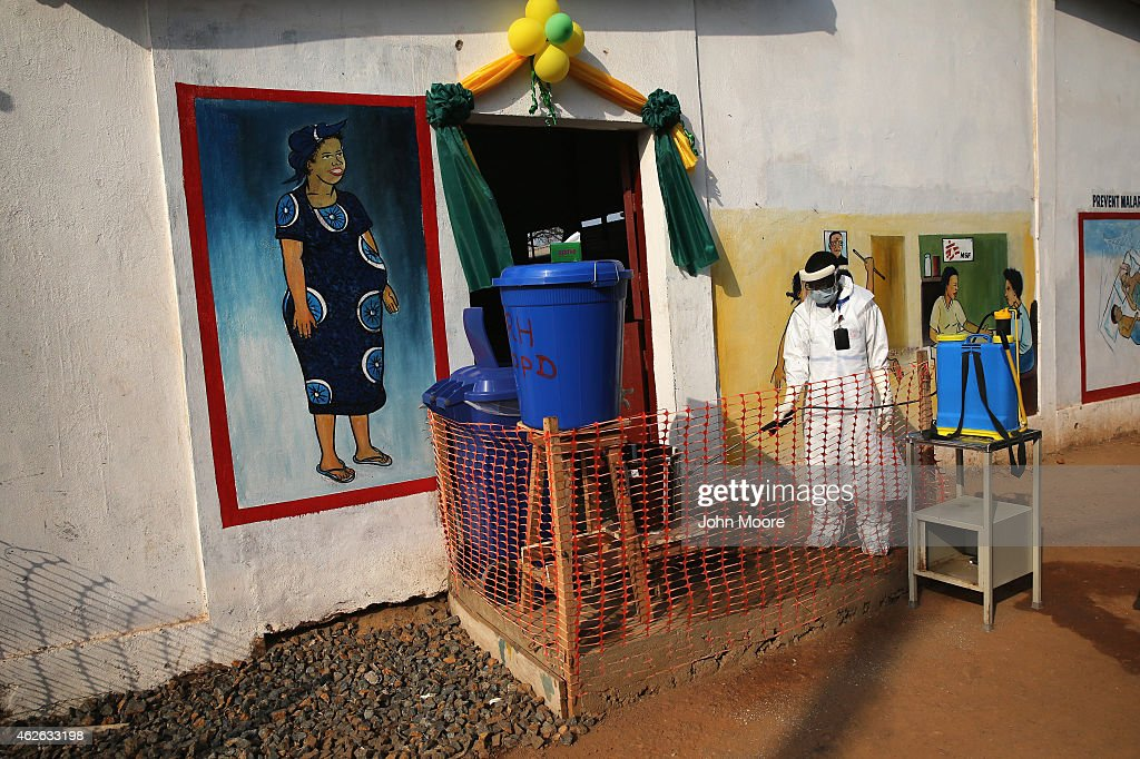 A health worker wearing protective clothing sprays the entrance of Redemption Hospital on February 1 2015 in Monrovia Liberia VIPs attended the...