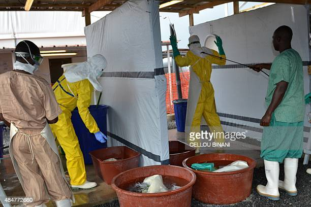 A health worker wearing protective gear is sprayed with disinfectant at the Nongo ebola treatment centre in Conakry Guinea on August 21 2015 The...