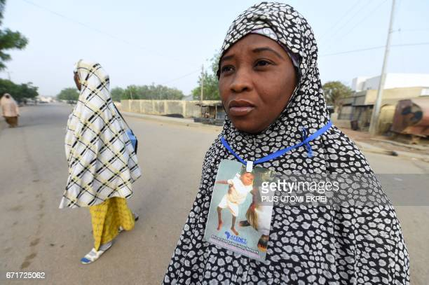 A health worker wears a badge with picture of a child infected by polio viruses during a vaccination campaign against polio at HotoroKudu Nassarawa...