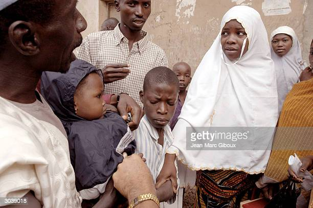 Health workers and the local chief pressure a woman to have her children vaccinated during the National Immunization Days November 13 2002 in Kano...