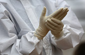 Health workers dress in protective clothing before taking the body of an Ebola victim from the Island Clinic Ebola treatment center on October 13...