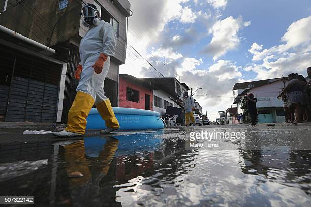 Health workers walk while fumigating in an attempt to eradicate the mosquito which transmits the Zika virus on January 28 2016 in Recife Pernambuco...