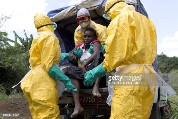 Health workers wearing protective suits assist a patient suspected of having Ebola on their way to an Ebola treatment centre run by the French Red...