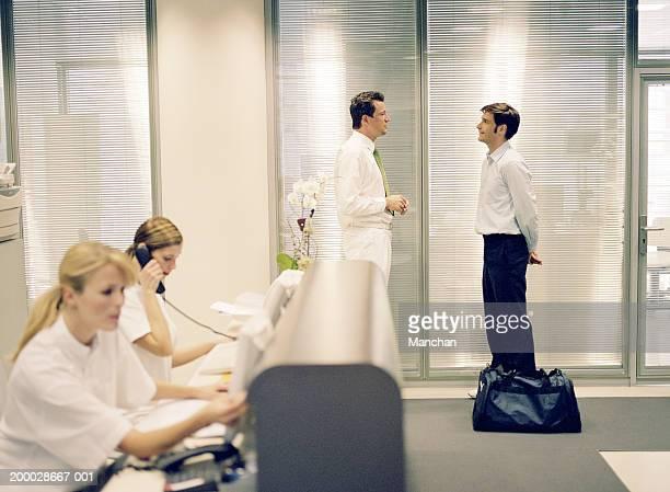 Healthcare centre reception (focus on men in background)