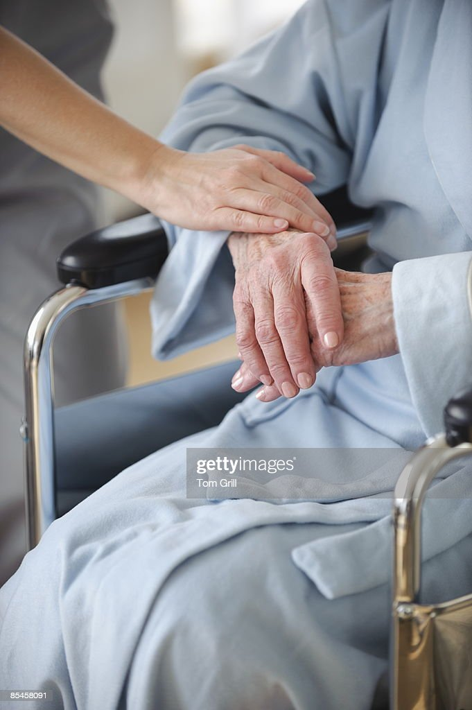 healthcare hands with senior hands in wheelchair : Stock Photo