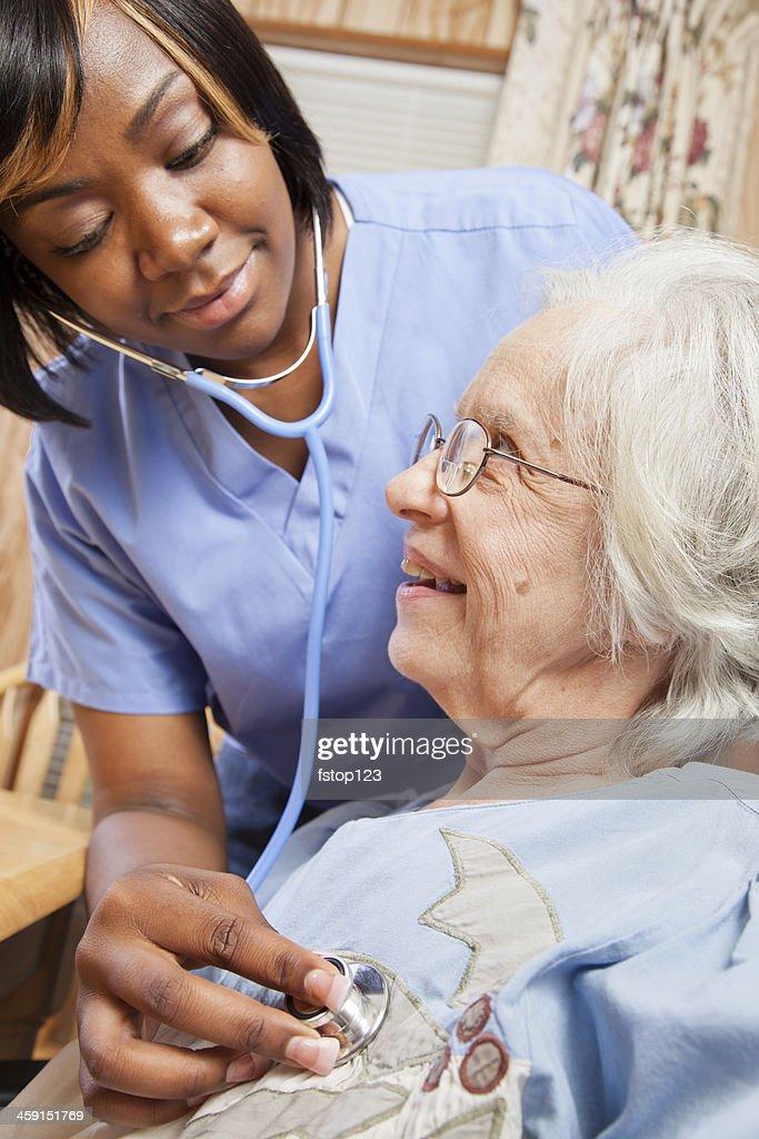 Healthcare: Home health nurse examines senior patient.
