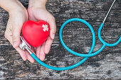 Healthcare medical insurance business and world heart health day concept with red heart on woman's hands support with doctor's stethoscope