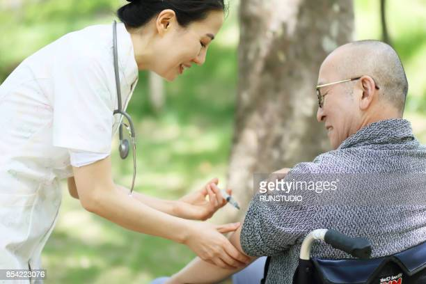 healthcare nurse giving injection to elderly man