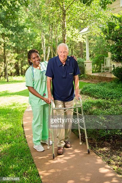 Healthcare: Nurse helps senior man outside using walker. Nursing home.