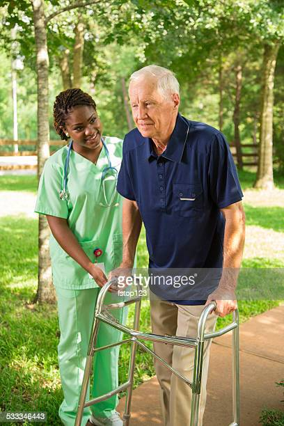 Healthcare: Nurse helps senior man outside using walker. Nursing home.