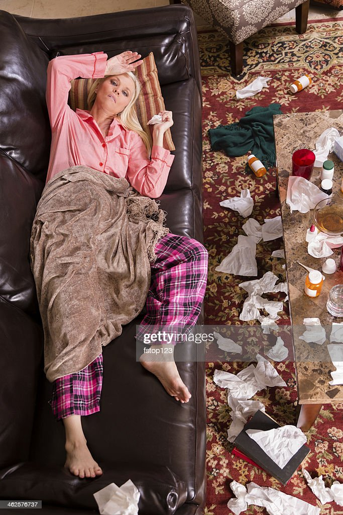 Healthcare:  Sick woman lies on couch with the flu.  Medications.