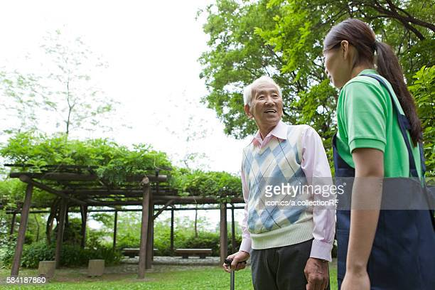 Healthcare worker and senior man with cane, Tokyo Prefecture, Honshu, Japan