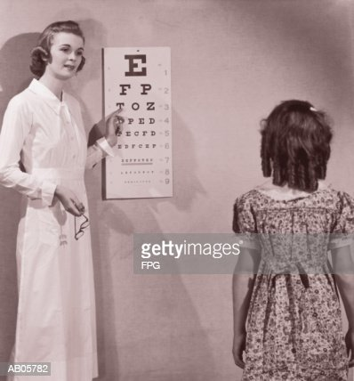 Healthcare worker giving girl (8-10) eye examination (B&W sepia) : Stock Photo