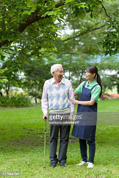 Healthcare worker helping senior man with cane, Tokyo Prefecture, Honshu, Japan