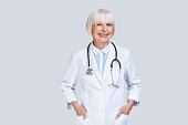Beautiful senior woman in lab coat looking at camera and smiling while standing against grey background