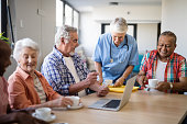 Healthcare worker serving coffee to senior people using laptop while sitting at table in nursing home