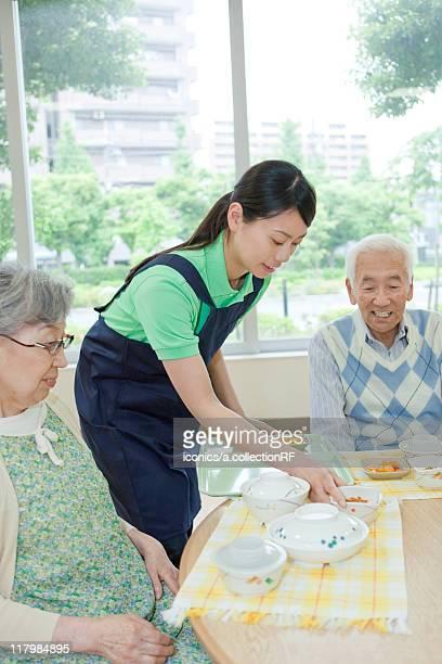 Healthcare worker serving food to senior people, Kanagawa Prefecture, Honshu, Japan