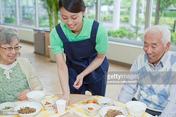 Healthcare worker serving food to senior woman, Kanagawa Prefecture, Honshu, Japan