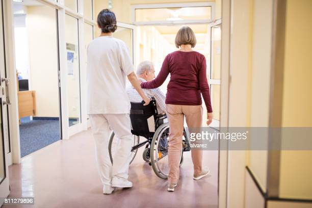 Mitarbeiter mit älteres Paar im Krankenhausflur