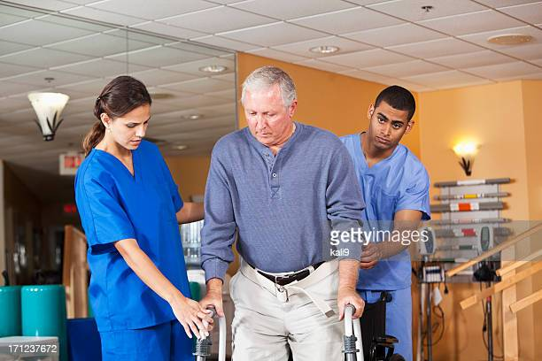 Healthcare workers helping senior man use walker