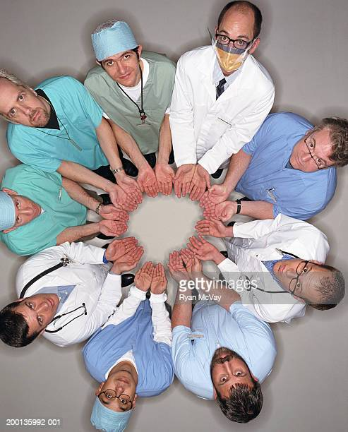 Healthcare workers standing in circle with cupped hands, overhead view