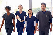 Healthcare workers walk through hospital with patient notes