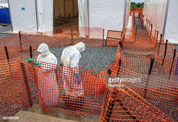 Healthcare workers wearing Personal Protective Equipment make their way to a tent with patient beds at an Ebola Treatment Center in Coyah Guinea on...