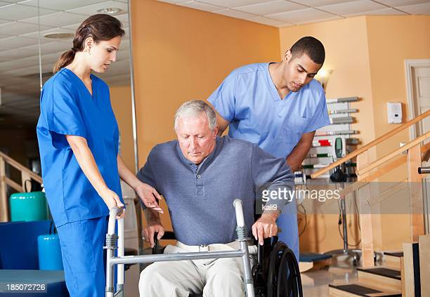Healthcare workers with senior man in wheelchair