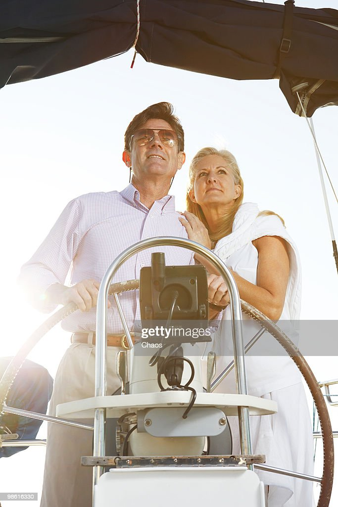 Healthy active couple on sailboat at sea.