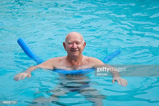 Healthy active senior man in swimming pool blue water copyspace