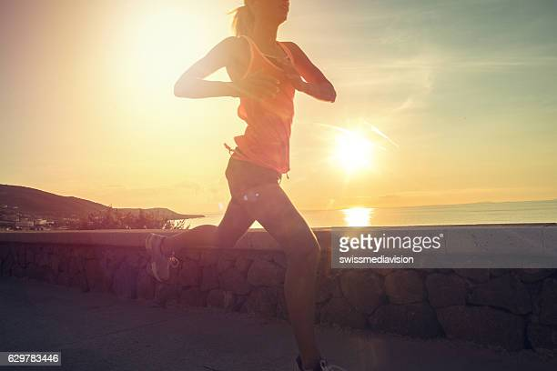 Healthy and sporty young woman running outdoors at sunset