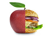 Healthy apple and unheatlhy burger merged into one over a white background