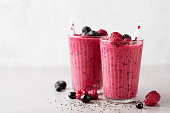 Tasty healthy dieting red berry smoothie with chia seeds in glasses on grey background. Closeup with copy space.