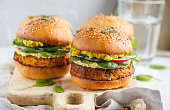 Healthy baked sweet potato burger with whole grain bun, guacamole, vegan mayonnaise and vegetables on a board. Vegetarian food concept, light background.