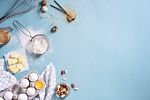 Healthy baking ingredients - flour, almond nuts, butter, eggs, biscuits over a blue table background. Bakery background frame. Top view, copy space.