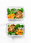 Healthy balanced lunch box. Grilled chicken zucchini burgers with broccoli, pumpkin, green pea salad on a light background, top view. Office food lunch healthy lifestyle concept