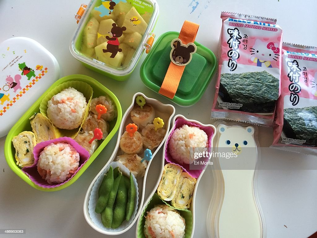 Healthy bento lunch boxes with rice balls edamame omelet fruits and seaweed