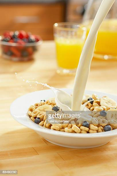 Healthy bowl of cereal with milk pour