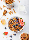 Healthy breakfast Fresh granola, muesli in bowl with milk and berries on a white background Top view
