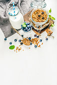 Healthy breakfast ingrediens. Homemade granola in open glass jar, milk or yogurt bottle, blueberries and mint on white wooden background, top view, copy space, vertical