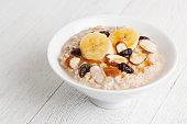 Healthy breakfast oatmeal bowl with bananas, almonds, raisins and honey