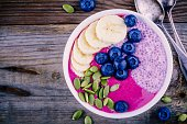 Healthy breakfast: purple smoothie bowl with chia pudding, banana, fresh blueberries and pumpkin seeds on wooden background