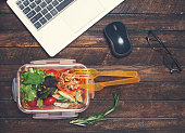 Healthy business lunch at workplace. Vegetables and fried chicken lunch box on working desk with laptop and glasses.
