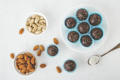 Healthy chocolate energy bites with nuts, dates, cocoa powder, coconut flakes on white table. Homemade gluten-free vegan healthy snacks top view.