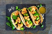 Roasted coconut cauliflower tacos. Healthy, vegan meal. Above view on a dark slate stone background.