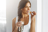 Diet. Nutrition. Vitamins. Healthy Eating, Lifestyle. Close Up Of Happy Smiling Woman Taking Pill With Cod Liver Oil Omega-3 And Holding A Glass Of Fresh Water In Morning. Vitamin D, E, A Fish Oil Cap