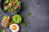 Healthy dinner background. Vegetable salad, sandwiches with fried egg and salmon, fresh green smoothie. Space for text. Healthy eating concept. Detox diet/plan. Top view. Weight loss. Food program