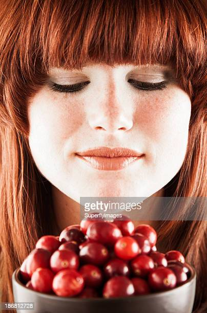 Healthy eating. Pretty redhead woman with bowl of fresh cranberries.