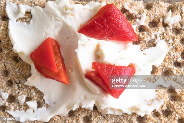 Healthy eating snack of cracker with cream cheese spread garnished with pickled pepper bell